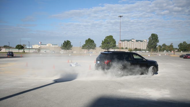 students participate in a skidpad course that teaches them how to control their car in slippery conditions