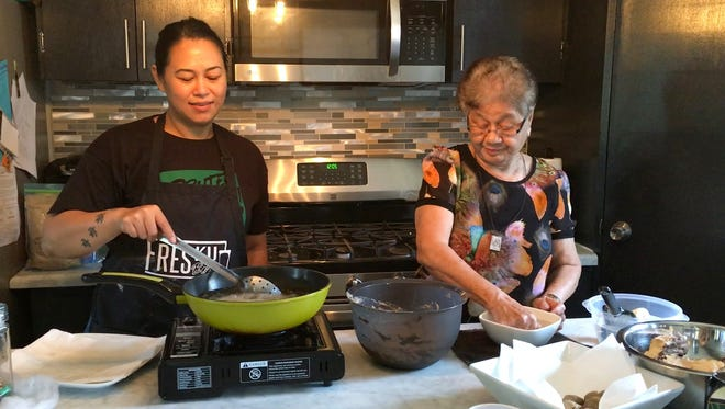 Amber Benavente-Sanchez, left, uses a spoon to stir frying buñelos dågu made by her and her grandmother, Vicenta S. Quichoco, right, on Dec. 15, 2017 in Mangilao.