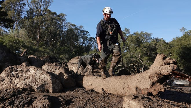 Decker, a search-and-rescue dog, works with handler Brent Brainard to clear a debris-filled creek bed in Montecito Friday.