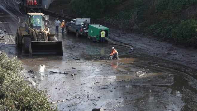 A worker tries to wrestle a shopping cart from the mud on Highway 101 in Montecito earlier this year.