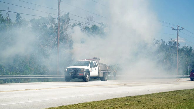 Fire crews work to contain flames along U.S. 41 East on Tuesday, March 27, 2018. Authorities closed U.S. 41 East between Six L's Farm Road and State Road 29 Tuesday afternoon due to heavy smoke and reopened the roadway shortly after 6 p.m.