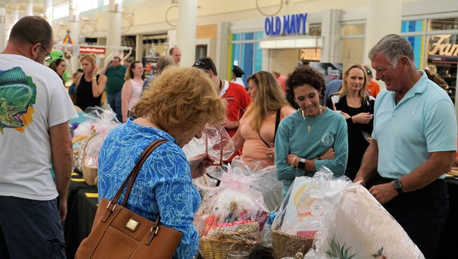 Shoppers look over auction items at the 2017 Art, Music & Benefit Auction at Treasure Coast Square mall. Jensen Beach Chamber of Commerce member businesses donate hundreds of items for the benefit auction. Auction donations are being accepted through April 20.