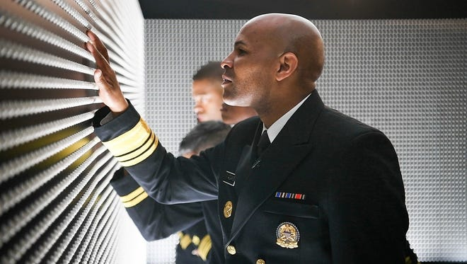 "Surgeon General Jerome Adams looks over ""The Pill Wall,"" a memorial at the White House in which pills depict the faces of people who died of opioid overdoses in 2015."