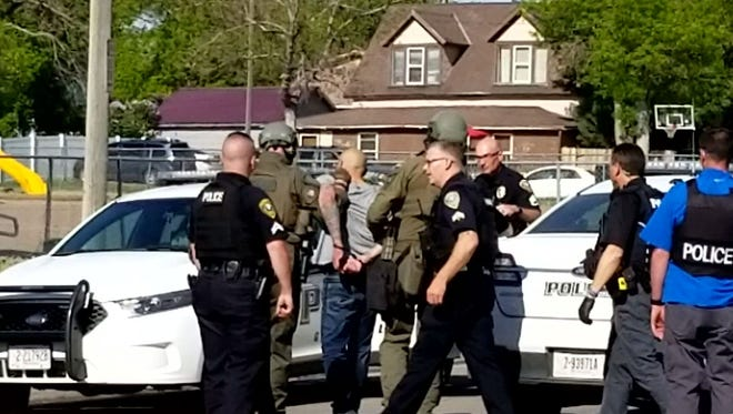 Police arrest a man outside across the street from Longfellow Elementary after a standoff that lasted about three hours Tuesday.