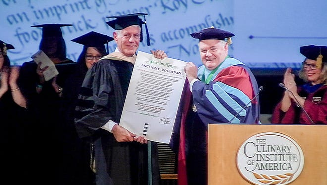 Culinary Institute of America President Tim Ryan presenting Anthony Bourdain with an honorary doctorate from the CIA on December 19, 2017.