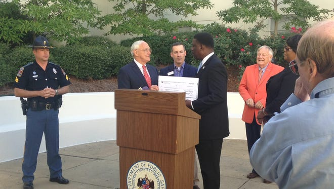 State Senator  Gerald Dial, center left, accepts a $5,000 donation from State Farm agent Willie Durham, center right.