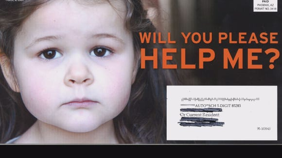 "A mailer makes the caption ""Will you help me please?"" over the face of a sad child the face of Proposition 122, a ballot measure aimed at getting Washington off Arizona's back."
