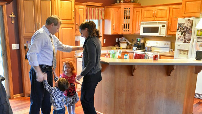 Chris Sutton catches up with his wife, Hope, and children, Anthony, 2, and Kaylyn, 3, at home after a day of work Nov. 4 at St. Cloud Hospital. Against the odds, Sutton, 45, has survived three bouts with cancer and one with heart disease.