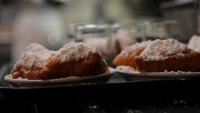 Beignets piled with powdered sugar at Cafe du Monde in New Orleans.