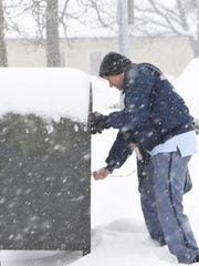 Brian Longfield, a postal worker, locks up a mailbox at Reservoir Square in the City of Poughkeepsie.