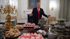 TOPSHOT - US President Donald Trump speaks alongside fast food he purchased for a ceremony honoring the 2018 College Football Playoff National Champion Clemson Tigers in the State Dining Room of the White House in Washington, DC, January 14, 2019. - Trump says the White House chefs are furloughed due to the partial government shutdown. (Photo by SAUL LOEB / AFP) (Photo credit should read SAUL LOEB/AFP/Getty Images)