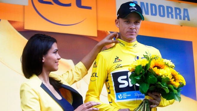 British rider Christopher Froome reacts on the podium after retaining the overall leader's yellow jersey following the ninth stage of the Tour de France.