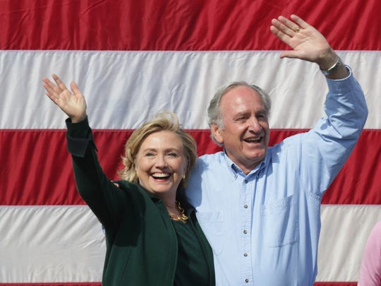 Sen. Hillary Clinton and Sen. Tom Harkin of Iowa wave to supporters during the 2014 Harkin Steak Fry on Sept. 14 in Indianola.