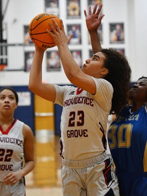 Providence Grove's Malea Garrison drives past Jordan-Matthews' Makayla Glover in a game last season. Garrison scored 33 points in the Patriots' victory Thursday night. [Paul Church/The Courier-Tribune]