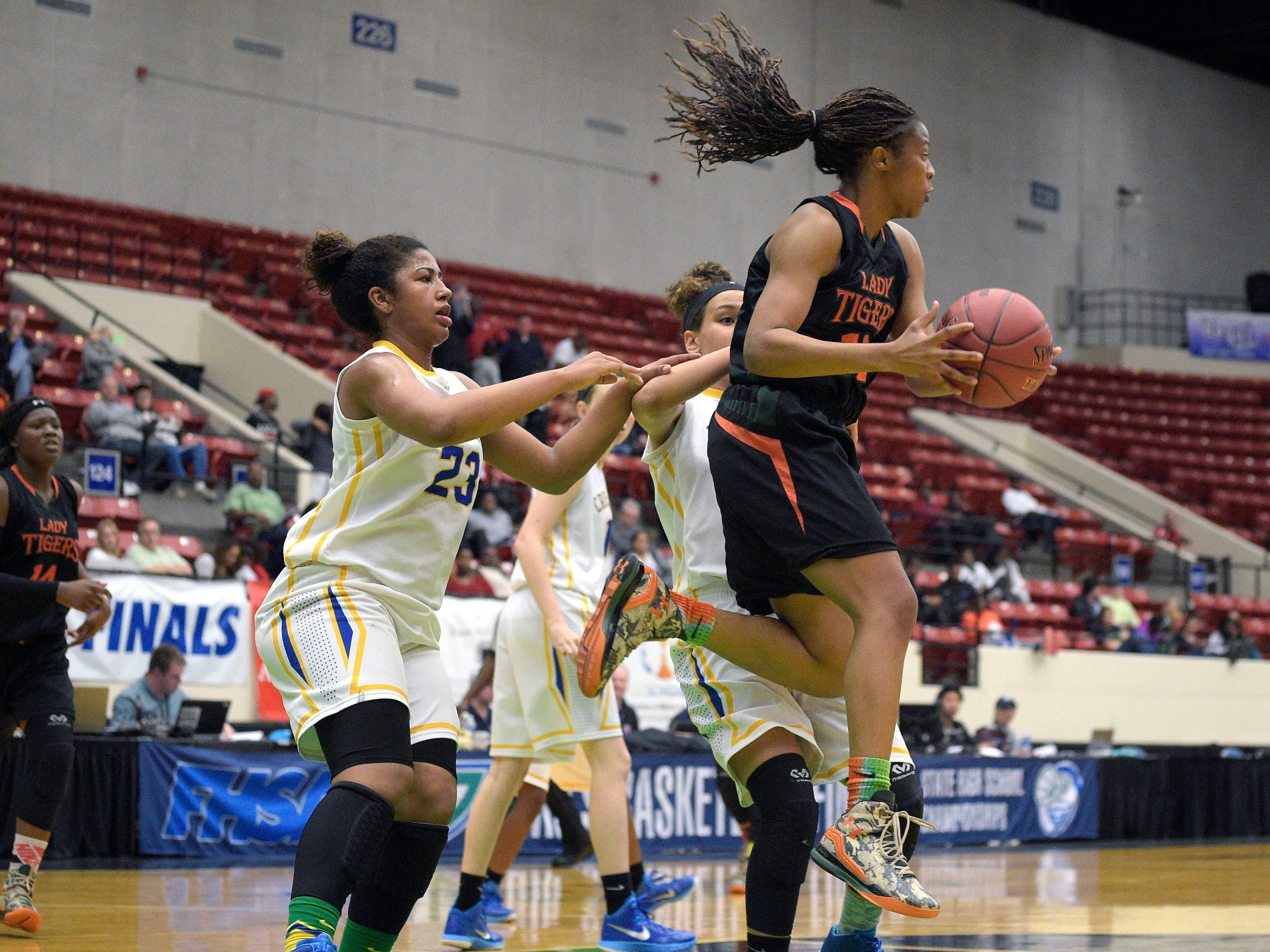 Dunbar's Kiara Desamours, right, grabs a rebound in front of Cardinal Newman's Milan Morris during Tuesday night's girls basketball Class 4A semifinal game in Lakeland. Desamours finished with 14 points in the victory.