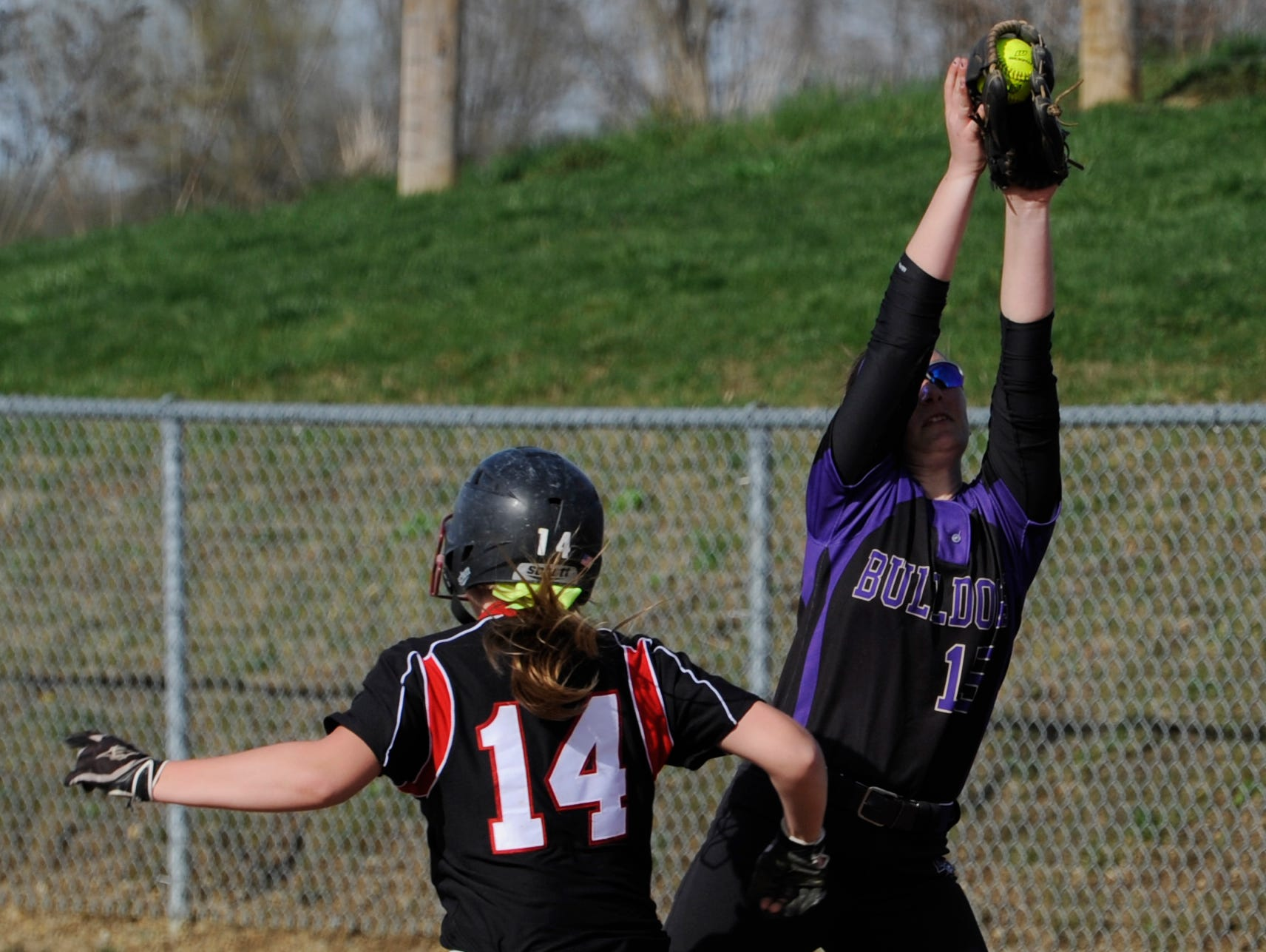 Liberty Union's Kailey Bolinger reaches first base as Bloom-Carroll's Hunter Gladman catches the ball at Bloom-Carroll High School. The Lions defeated the Bulldogs 1-0.