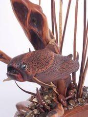 This piece is handcrafted out of a multitude of woods, including cocobolo wood from South America, which the fish is made from; the cattails are Tiger Wood from Brazil; the Branch is Diamond Willow right from the local Sun River; the rocks come from the North Fork of the Sun River; and the base is Jatoba from Africa. The piece would sell for $9,000.