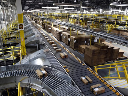 Packages ride on a conveyor system at an Amazon fulfillment center in Baltimore. Amazon, Walmart and others are promising to deliver more of their goods in a day and this holiday season will be the first real test of whether they can make that happen.