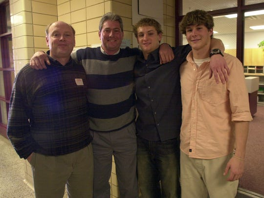 The Colquitt family gets together after Britton Colquitt, right, signed a football scholarship with the University of Tennessee in 2003 at Bearden High School. From left, his father, Craig Colquitt, cousin Jimmy, and brother Dustin. (News-Sentinel photo by Paul Efird)