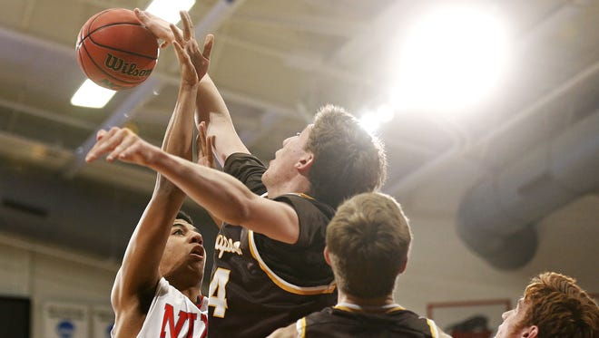 Nixa High School forward Christian Bundy (35) has a shot blocked by Kickapoo High School forward Jared Ridder (34) during the Class 4 sectional playoff game between Nixa and Kickapoo played at the O'Reilly Family Event Center in Springfield, Mo. on March 9, 2016.
