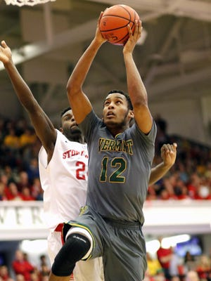 Vermont's Darren Payen is defended by Stony Brook's Roland Nyama as he drives to the hoop in the America East championship game at Stony Brook, N.Y. on Saturday.