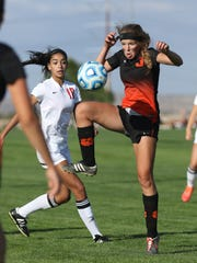 Aztec's Grace Olson, right, receives a pass against Albuquerque Academy on Thursday at the Bernalillo Soccer Complex.