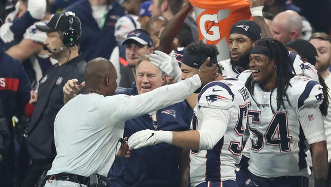 Brian Flores (left), Bill Belichick (center) and Kyle Van Noy celebrate amid the traditional Gatorade bath after the Patriots beat the Los Angeles Rams in the Super Bowl. Later, linebacker Elandon Roberts doused Flores a second time with Gatorade.