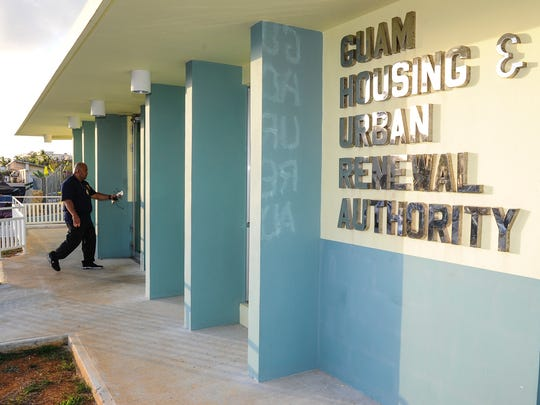 In this file photo, an investigator enters the Guam Housing and Urban Renewal Authority office building in Sinajana after the close of business on June 10, 2016.