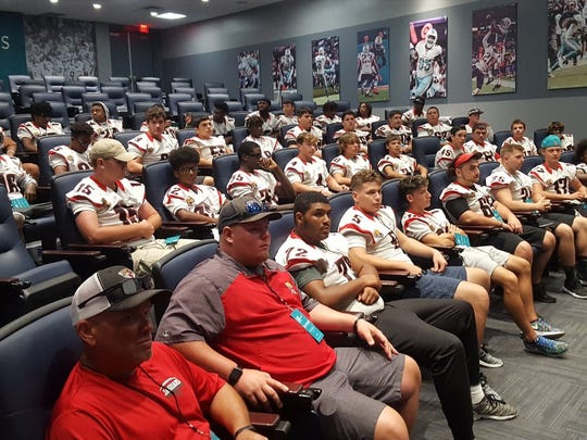 Port St. Lucie players and coaches sit in a Dolphins team meeting room for a talk from former Dolphins player Terry Kirby on Wednesday in Davie.
