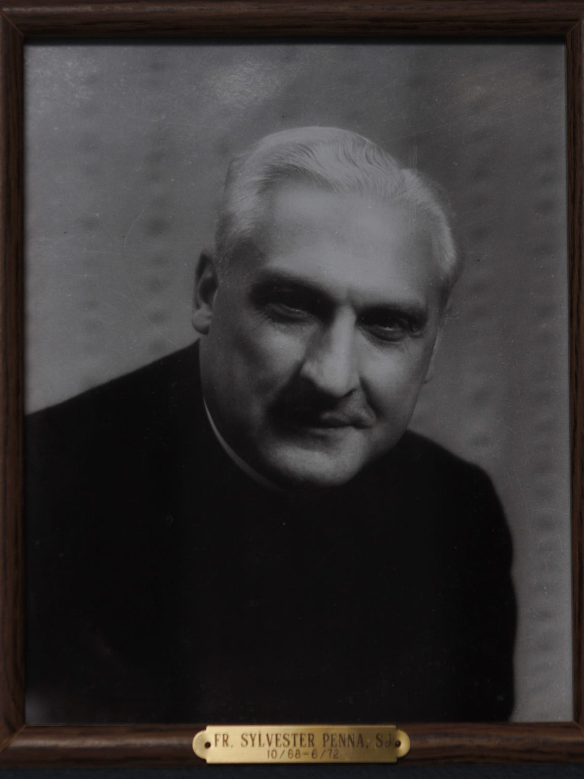 Father Sylvester Penna's portrait hangs among the other priests who have served the St. Thomas Catholic Church in Harlem.