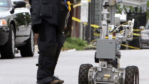 A Westchester County police bomb squad technician lifts the crime scene tape for his robot near a parking lot on Van Cortlandt Park Avenue in Yonkers while police investigate a van in a parking lot that was linked to a large amount of weapons in a Yonkers home Sept. 8, 2012.