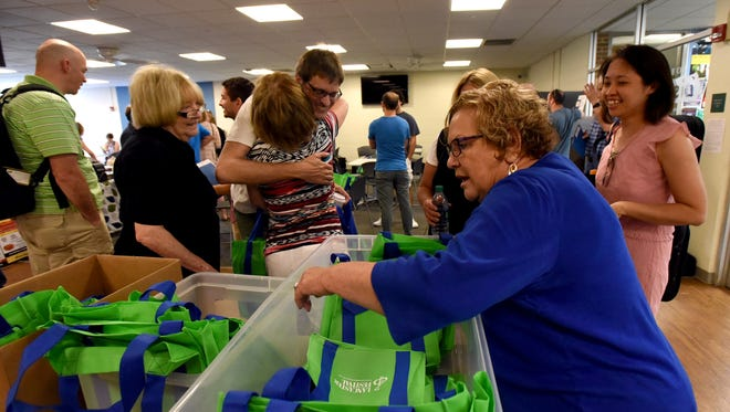 SallyAnn Haase, right, looks through bins for an orientation bag whileTammy Loft hugs Victor Dome Tuesday, July 18, 2017, at Ohio University Lancaster. Haase, Loft, Jeanette Acton, left, and other volunteers were helping hand out packets to Lancaster Festival Orchestra members as they arrived for orientation.