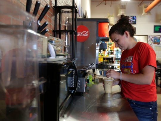 Hunter Hilber, 19, of Arpin, makes a drink for a customer