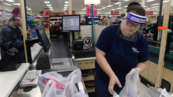 Cashier Skyla McDonald bags groceries for a customer May 12 at Sander's Market in North East. The store is taking precautions for its employees and customers during the COVID-19 pandemic.
