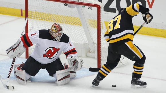 Pittsburgh Penguins' Sidney Crosby (87) works with the puck before scoring on New Jersey Devils goaltender Keith Kinkaid (1) during the first period of an NHL hockey game in Pittsburgh, Friday, March 23, 2018. (AP Photo/Gene J. Puskar)