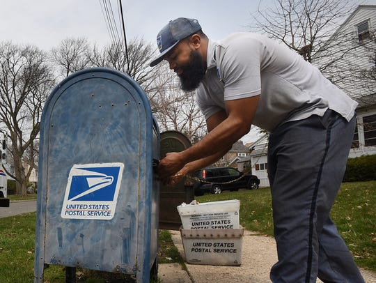 A U.S. Postal Service letter carrier empties a collection box. Police in Toms River are investigating incidents of mailbox fishing.