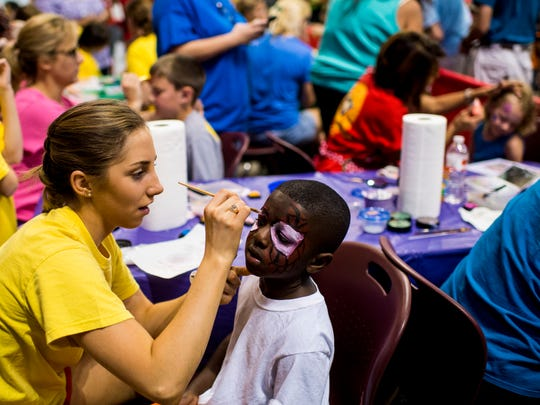 Remi Coco paints the face of Atrelle Guilliam, 4, during the Games of Acadiana at the Cajundome in Lafayette in 2015. The event is the primary fundraising event for Miles Perret Cancer Services which provides support services for cancer patients and their families in Acadiana