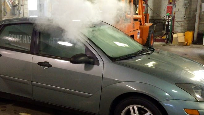 Simulated marijuana smoke billows from a specially equipped car being used by Colorado traffic-safety officials to draw attention to state laws prohibiting marijuana users from getting behind the wheel while stoned.