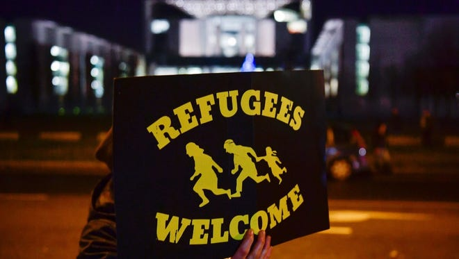 A woman holds a 'Refugees Welcome' sign outside the building in Berlin that houses German Chancellor Angela Merkel's office.