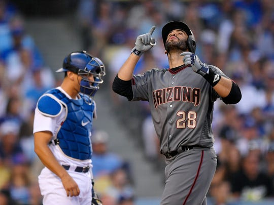 Arizona Diamondbacks' J.D. Martinez, right, gestures as he scores after hitting a solo home run as Los Angeles Dodgers catcher Austin Barnes stands at the plate during the seventh inning of a baseball game, Monday, Sept. 4, 2017, in Los Angeles. This was his second home run of the game. (AP Photo/Mark J. Terrill)