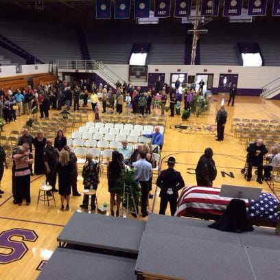 A line of mourners winds across the floor at the Muncie
