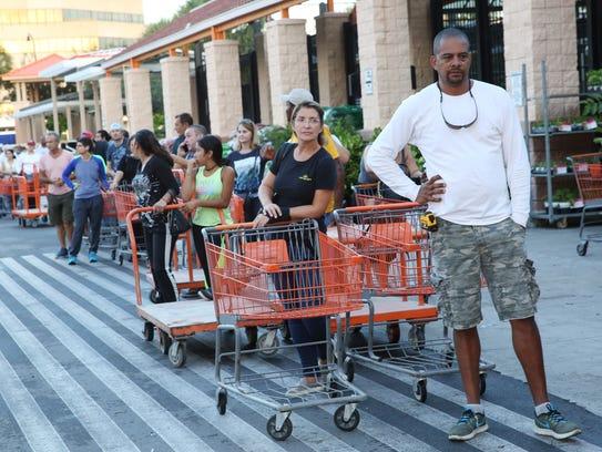Eduardo Soriano of Miami, waits in a line since dawn