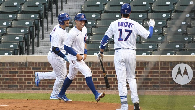 Chicago Cubs outfielder Ian Happ, left, is greeted by Nico Hoerner, center, and Kris Bryant (17) after hitting a two-run home run against the Milwaukee Brewers during the third inning of an opening day game Friday, July, 24, 2020, in Chicago.