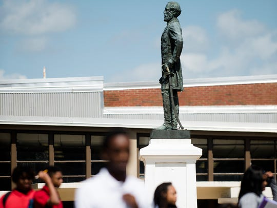 Lee High School students walk past the statue of General