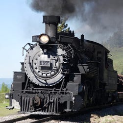 A Cumbres & Toltec steam train blasts steam from its boiler as it descends Cumbres Pass toward Chama, N.M. after crossing the border from Colorado during a train-engineer class.