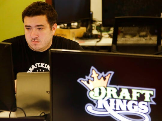 FILE- In this Sept. 9, 2015, file photo Len Don Diego, marketing manager for content at DraftKings, a daily fantasy sports company, works at his station at the company's offices in Boston. The daily fantasy sports industry has contracted starkly since questions about the legality of online games offered by companies sparked court and legislative battles across the U.S. last year.