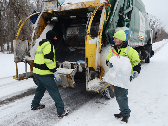 Tony Thompson, left, and Eric Rue collect trash for