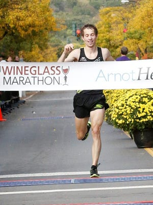 Bryan Morseman crosses the finish line Sunday in Corning to win the Wineglass Marathon for the third time.