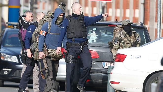 Police officers take position during a police operation in Forest, Brussels, Belgium, 15 March 2016. A shooting took place during a police raid linked to the Paris terrorist attacks. According to reports, two members of federal police were injured in the operation and police were still searching for the shooter.  EPA/LAURENT DUBRULE