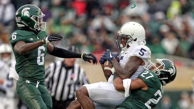 Penn State Nittany Lions wide receiver DaeSean Hamilton is tackled by Michigan State Spartans safety Khari Willis during the second quarter of a game at Spartan Stadium.
